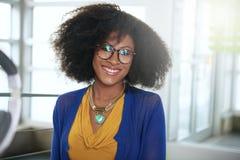 一名微笑的妇女的画象有一个非洲的在计算机在明亮的玻璃办公室 免版税图库摄影