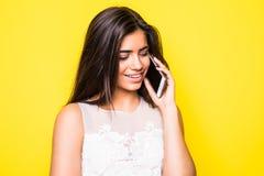 一名微笑的妇女的画象谈话在黄色背景的电话 免版税库存图片