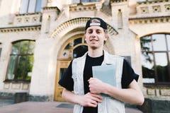 一名微笑的学生的画象一个盖帽和笔记本的在他的以大学大厦为背景的手上 免版税库存图片