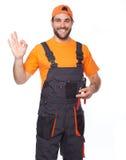 一名微笑的工作者的画象拿着钳子的蓝色制服的 免版税库存图片