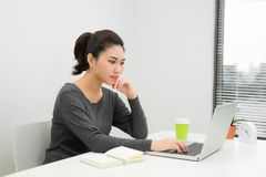 一名微笑的年轻女实业家的画象有膝上型计算机的在brigh 图库摄影