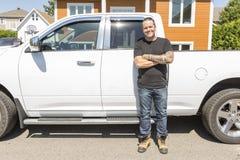 一名微笑的建筑工人的画象站立在建造场所的卡车旁边的安全帽的 免版税库存照片