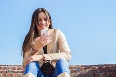 一名微笑的美丽的妇女短信的sms的画象 图库摄影