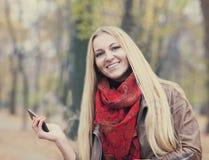 一名微笑的美丽的妇女短信的sms的画象 免版税库存照片