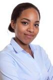 一名微笑的非洲妇女的画象一件蓝色衬衣的 免版税库存图片