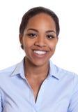 一名微笑的非洲妇女的画象一件蓝色衬衣的 库存照片