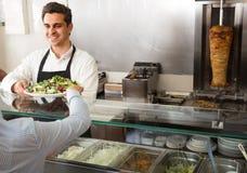 一名微笑的年轻男性快餐工作者的画象 库存照片
