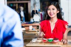 一名快乐的亚裔在一家凉快的咖啡店的妇女预定的杯形蛋糕的画象 库存照片