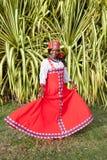 一名快乐的非裔美国人的妇女的垂直的充分的身体一件明亮的五颜六色的全国俄国礼服的 免版税图库摄影