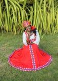 一名快乐的非裔美国人的妇女的垂直的充分的身体一件明亮的五颜六色的全国俄国礼服的 免版税库存照片