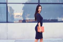 一名性感的深色的女实业家在穿戴了黑正式衣裳,并且高跟鞋,拿着一台片剂计算机去工作 免版税图库摄影