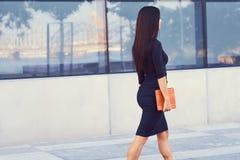 一名性感的深色的女实业家在穿戴了黑正式衣裳,并且高跟鞋,拿着一台片剂计算机去工作 免版税库存图片