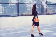 一名性感的深色的女实业家在穿戴了黑正式衣裳,并且高跟鞋,拿着一台片剂计算机去工作 图库摄影