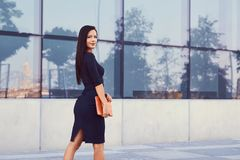 一名性感的深色的女实业家在穿戴了黑正式衣裳,并且高跟鞋,拿着一台片剂计算机去工作 免版税库存照片