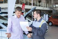 一名恼怒的顾客谈话与汽车修理服务的一位技工 免版税库存照片