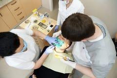 一名患者的顶视图有闭合的眼睛的在一把扶手椅子和牙医有仪器的 库存图片