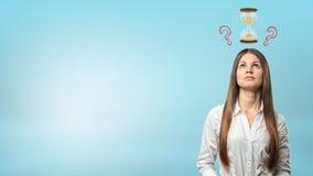 一名想法的女实业家和在她的头上的问号的画象有小滴漏的 库存图片