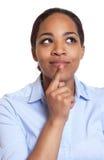 一名想法的非洲妇女的画象一件蓝色衬衣的 库存照片