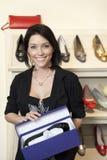 一名愉快的中间妇女的画象有鞋类箱子的在鞋店 免版税库存照片
