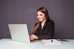 一名愉快的偶然女实业家的画象坐在她的工作场所的毛线衣的在办公室 免版税库存图片