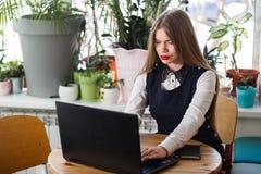 一名愉快的偶然女实业家的画象坐在她的工作场所的毛线衣的在办公室 免版税图库摄影