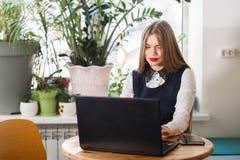 一名愉快的偶然女实业家的画象坐在她的工作场所的毛线衣的在办公室 免版税库存照片