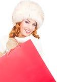 一名愉快的妇女在冬天穿衣与购物袋 图库摄影