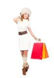 一名愉快的妇女在冬天穿衣与购物袋 免版税库存照片