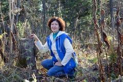 一名愉快的妇女在树桩旁边坐在秋天森林里 免版税库存图片