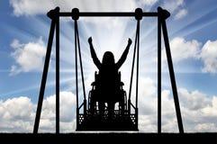 一名愉快的妇女的剪影是一个轮椅的一废人在障碍人们的能适应的摇摆 免版税库存图片