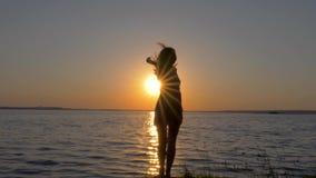 一名愉快的妇女的剪影美妙地和温文地跳舞在海的日落 股票录像