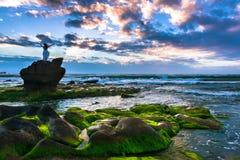 一名愉快的妇女站立在巨石城顶部在海滩并且享受自由在日出 库存图片