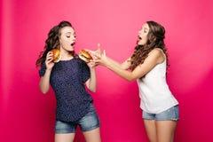 一名愉快的妇女简而言之拿着汉堡包,女朋友高兴夺走 开放她的嘴,女孩是 免版税库存照片