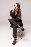 一名愉快的快乐的妇女的画象黑开会在椅子和看的照相机在灰色背景 库存照片