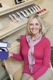 一名愉快的成熟妇女的画象有鞋盒的在鞋类商店 图库摄影