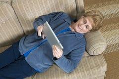 成熟资深年长妇女用途Ipad计算机 免版税库存照片