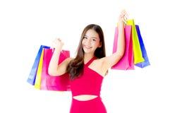 一名愉快的激动的亚裔妇女的0portrait红色礼服身分和购物袋的 库存图片