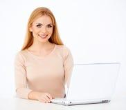一名愉快的白肤金发的妇女的纵向她的服务台的 库存图片
