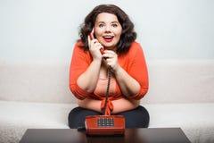 一名愉快的肥胖妇女的画象有电话的 免版税库存照片