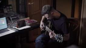 一名成人职业音乐家,使用在一把电吉他的人们的画象坐在录音的一把椅子 股票视频