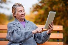 一名成熟妇女坐长凳并且接触片剂 外部在秋天公园 免版税库存照片