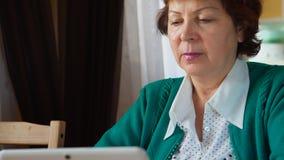 一名成熟妇女的画象在家使用一台白色片剂个人计算机 免版税图库摄影
