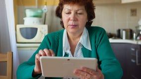 一名成熟妇女的画象在家使用一张白色片剂个人计算机-正面图 免版税库存图片