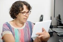 一名成熟妇女的画象有一种数字式片剂的 免版税库存图片