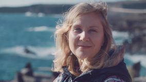 一名成熟白肤金发的妇女的特写镜头画象有微笑的在她的面孔和开发的头发在风反对波浪  股票视频