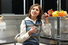 一名新深色的妇女在一个现代厨房里 库存图片