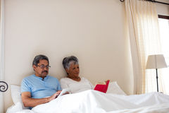读一名新颖和老人的资深妇女使用数字式片剂在床 免版税库存照片
