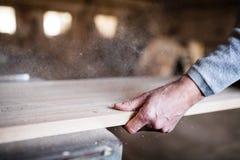 一名无法认出的人工作者在木匠业车间,与木头一起使用 免版税库存照片