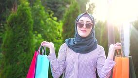 一名时髦的年轻回教妇女的画象有袋子的在她的在购物以后的手上 股票视频