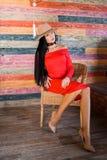 一名时髦的深色的妇女的画象戴一个红色礼服、米黄鞋子和帽子和坐椅子 免版税库存照片